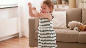 Bebé feliz que salta y que se divierte en casa almacen de metraje de vídeo