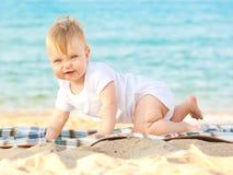 Bebé feliz que se relaja en la playa Imagenes de archivo