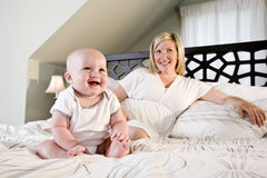 Bebé feliz que se sienta en cama con la madre Foto de archivo