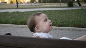Bebé feliz que se sienta en el banco en parque metrajes