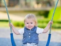Bebé feliz que se sienta en el oscilación Fotografía de archivo libre de regalías