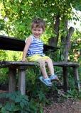 Bebé feliz que se sienta en jardín Imagenes de archivo