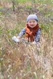 Bebé feliz que se sienta en la hierba Foto de archivo