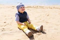 Bebé feliz que se sienta en la orilla del lago Fotografía de archivo