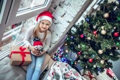 Bebé feliz que se sienta en la ventana con el regalo de Navidad imágenes de archivo libres de regalías