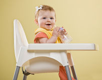 Bebé feliz que senta-se no highchair Foto de Stock Royalty Free