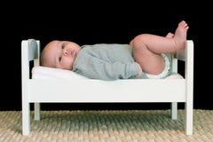 Bebé grande en una pequeña cama Imagen de archivo