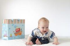 Bebé gritador con un paquete del regalo Niño triste en histeria imagenes de archivo