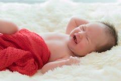 bebé gritador que miente en cama imagen de archivo