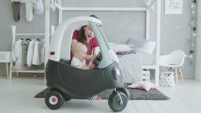 Bebé gritador que quiere jugar sin la ayuda de la mamá almacen de metraje de vídeo