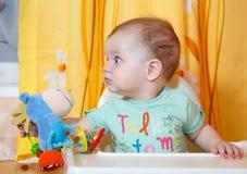 Bebé hambriento con el juguete en su comida que espera de la mano para Foto de archivo