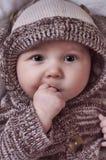 Bebé hermoso con las manos en boca Imagenes de archivo