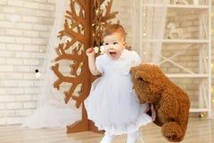 Bebé hermoso con un oso de peluche marrón suave en el interior Foto de archivo