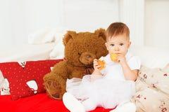 Bebé hermoso con un oso de peluche marrón suave en el interior Fotos de archivo