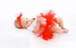 Bebé hermoso de la niña en falda roja en cama Fotos de archivo libres de regalías