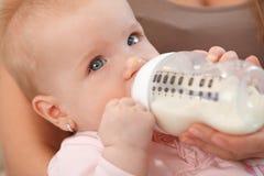 Bebé hermoso del primer con la botella de oficio de enfermera Imagenes de archivo