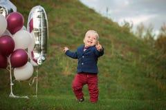 Bebé hermoso del retrato de la sonrisa Muchacho lindo de 1 año en la hierba Aniversario del cumpleaños foto de archivo