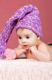 Bebé hermoso en casquillo hecho punto Foto de archivo