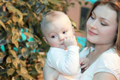 Bebé hermoso en sus manos de las madres. Foto de archivo
