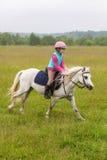 Bebé hermoso en un galope del caballo blanco Imagen de archivo libre de regalías