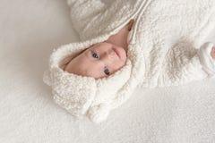 Bebé hermoso en un traje blanco caliente que miente en una cama foto de archivo