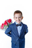 Bebé hermoso en un traje con un ramo de rosas rojas en un fondo blanco Foto de archivo