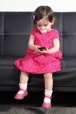 Bebé hermoso que juega con un teléfono elegante en casa Imágenes de archivo libres de regalías
