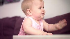 Bebé hermoso que se coloca en el sofá Niño dulce que aprende caminar metrajes