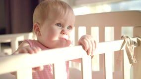 Bebé hermoso que se coloca en pesebre Niño que aprende colocarse en cama en casa almacen de video