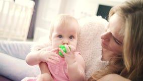 Bebé hermoso que se sienta en abrazo de la madre Niña pequeña con el juguete en boca almacen de video