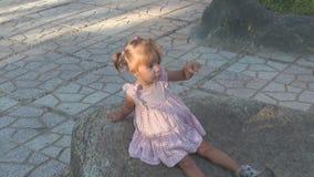 Bebé hermoso que se sienta en una roca grande Ella está llevando un vestido Ella mira el cielo y en los lados el bebé vio algo, e almacen de metraje de vídeo