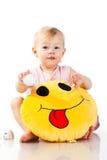 Bebé hermoso que sostiene una almohadilla Fotos de archivo