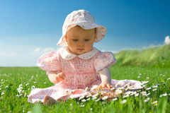 Bebé hermoso sentado en campo imagenes de archivo