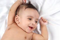 Bebé indio sonriente en el fondo blanco del satén Imagenes de archivo