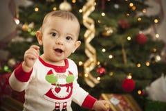 Bebé infantil de la raza mixta que disfruta de mañana de la Navidad cerca del árbol Imagenes de archivo