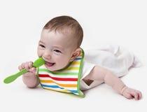 Bebê infantil de sorriso com a colher na boca fotografia de stock royalty free