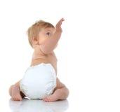 bebé infantil del niño de 6 meses que se sienta con la mano aumentada para arriba Fotos de archivo
