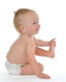 Bebé infantil del niño que sienta y que lleva a cabo la pierna feliz Fotografía de archivo libre de regalías