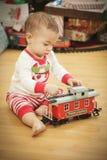 Bebé infantil que disfruta de mañana de la Navidad cerca del árbol Foto de archivo libre de regalías