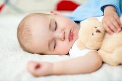 Bebé infantil que duerme con el juguete de la felpa Fotos de archivo