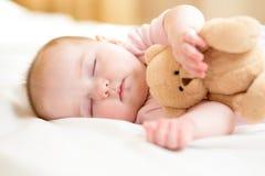 Bebé infantil que duerme con el juguete de la felpa Imagen de archivo libre de regalías