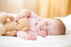 Bebé infantil que duerme con el juguete de la felpa Imagenes de archivo