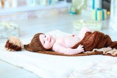Bebé infantil que miente en la manta en sombrero con el bubón Imagen de archivo libre de regalías
