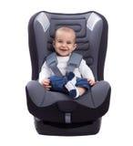 Bebé infantil sonriente que se sienta en un asiento de carro, aislado en blanco Imagen de archivo libre de regalías
