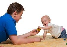 Bebé inquisitivo feliz que juega al hermano del withbig Imagen de archivo