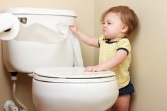 Bebé intratable que tira del papel higiénico Fotografía de archivo libre de regalías