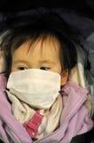 Bebé japonés que desgasta una mascarilla Foto de archivo libre de regalías
