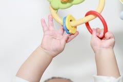 Bebé japonés que estira sus manos al juguete Imagenes de archivo