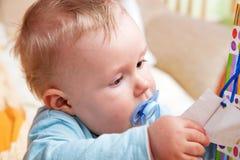 Bebé joven con un maniquí en su boca fotos de archivo libres de regalías