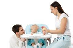 Bebé joven de la alimentación de los padres. Fotos de archivo